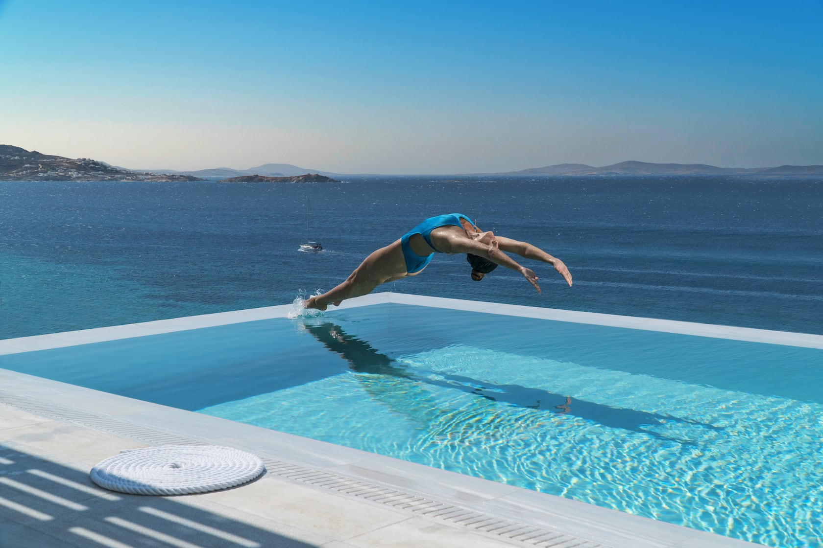 Lady diving with an impressive way into the infinity pool with sea views at Mykonos Riviera.