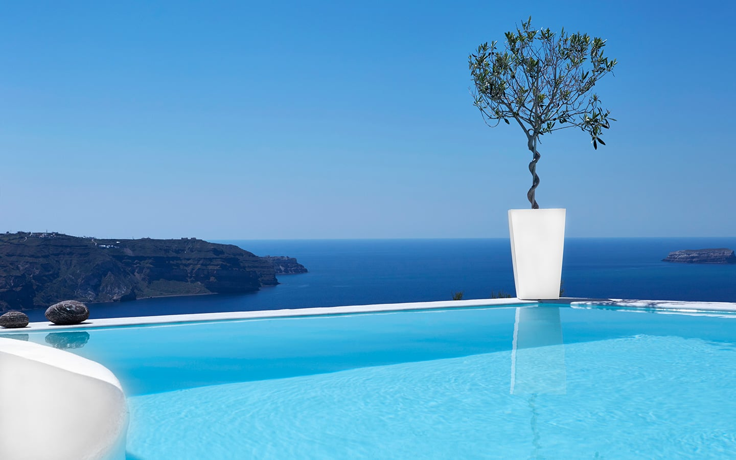 Crystal clear infinity pool overlooking the sea in Athermi Suites Santorini.