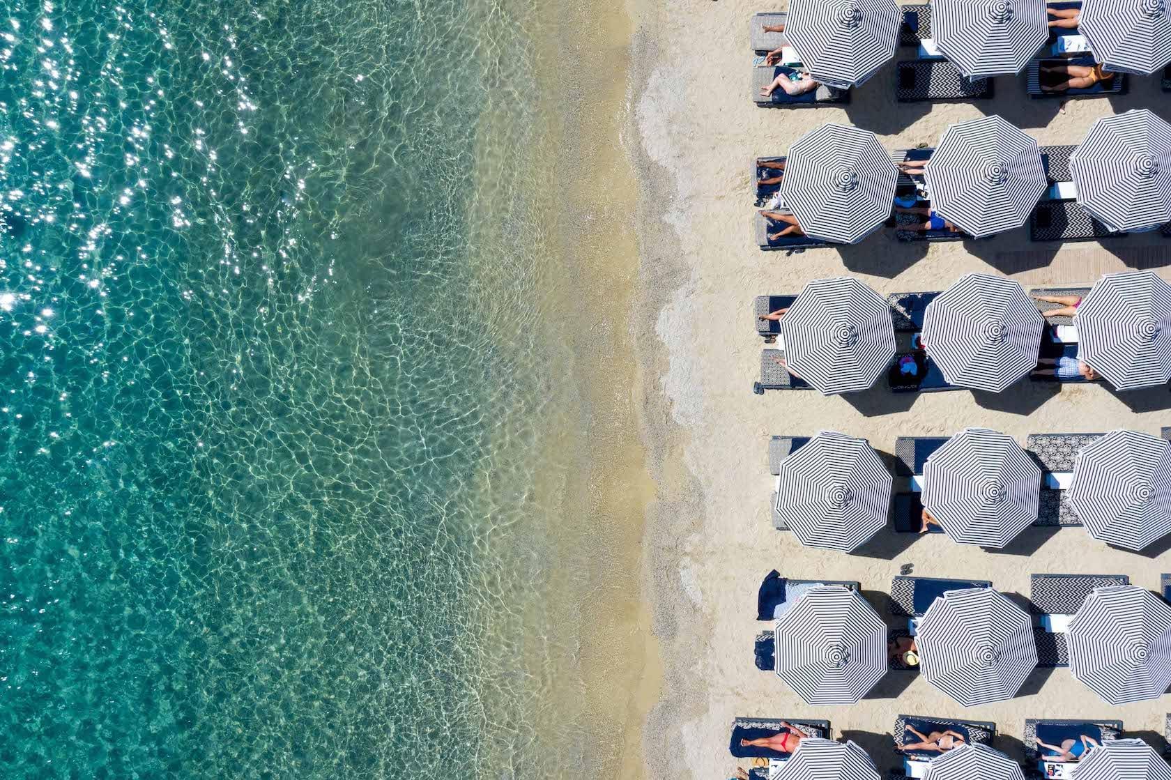 Overhead view of sun umbrellas and the beach of Ornos in Mykonos.