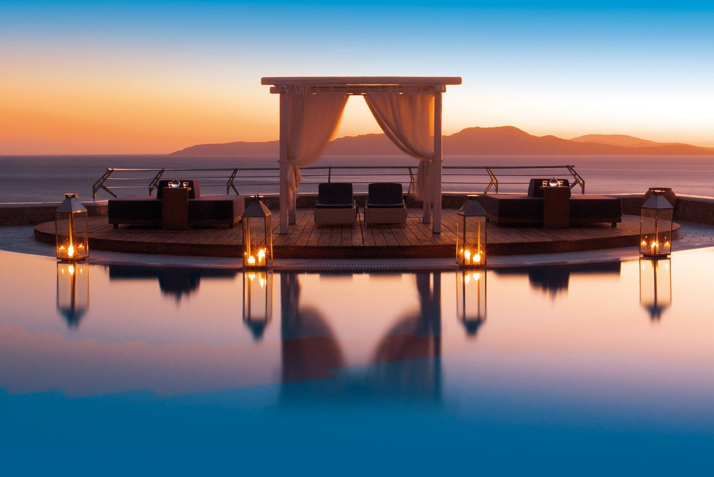 Sitting area by the crystal clear pool overlooking the Aegean sea at sunset.