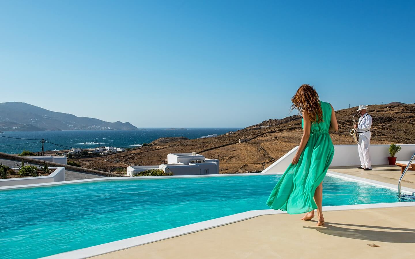 Lady in a green dress standing near the pool overlooking the sea at Just White VIP Villas Mykonos.