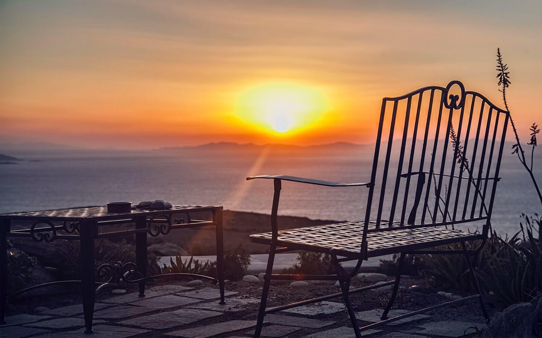 Outdoor sitting area overlooking the sea at sunset at Just White VIP Villas Mykonos.