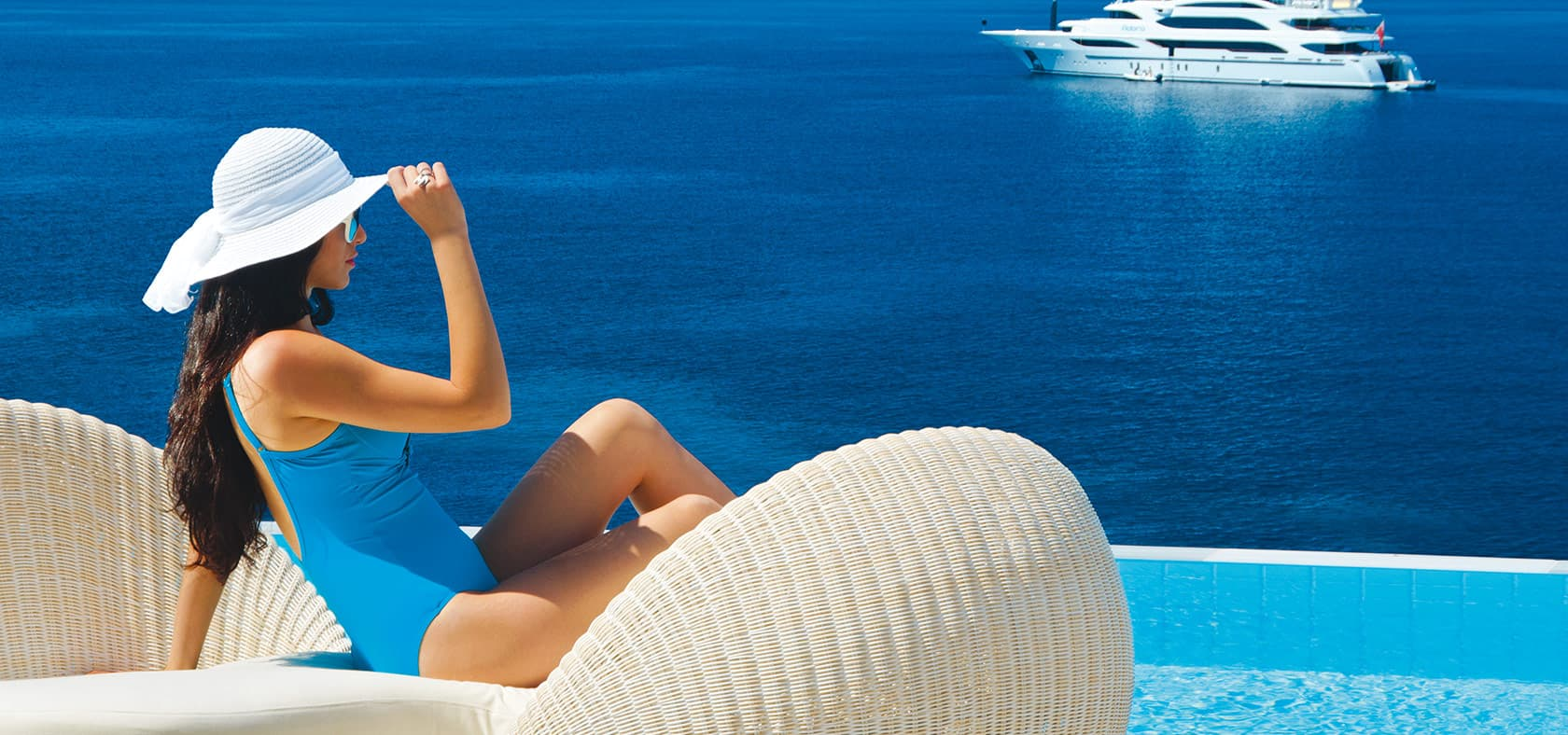 Lady in swimsuit and hat sitting by the edge of the pool overlooking the sea.