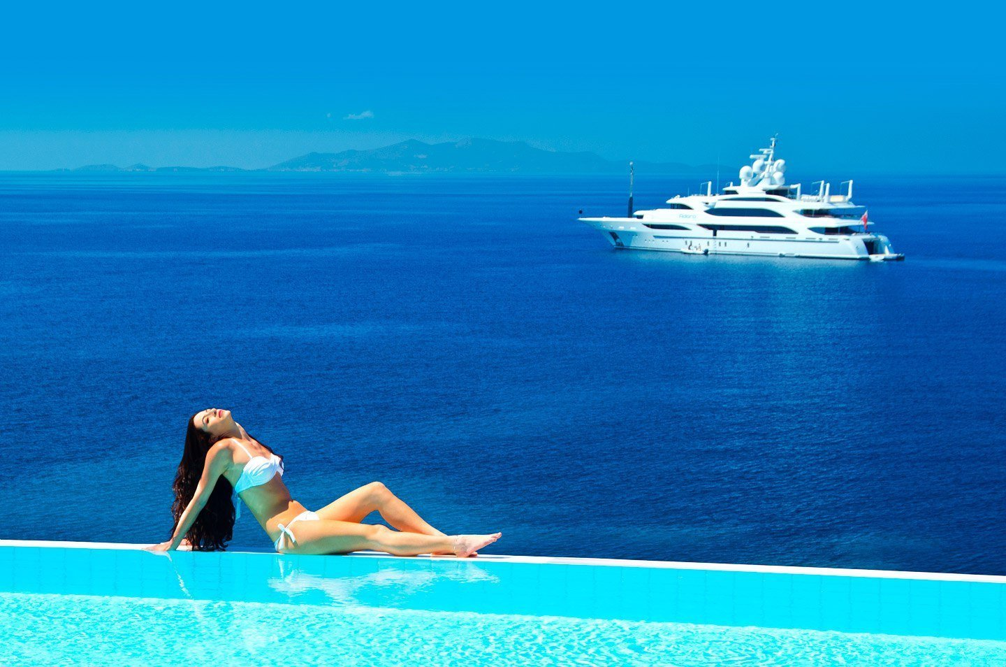 Lady sitting by the edge of an infinity pool overlooking the sea and a yacht.