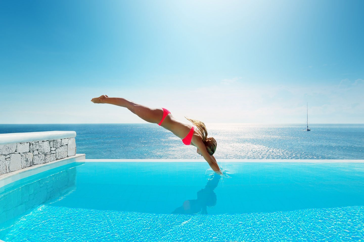 Lady in a red swimsuit diving into an infinity crystal clear pool overlooking the sea.